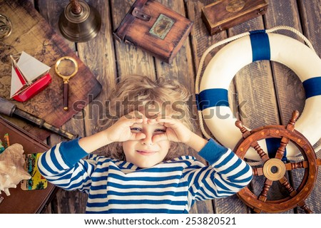 Happy kid playing with vintage nautical things. Child having fun at home. Travel and adventure concept. Unusual top view portrait - stock photo