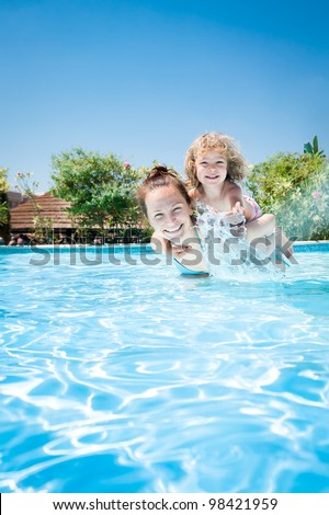 Happy kid playing with woman in swimming pool on a tropical resort at the sea. Summer vacations - stock photo