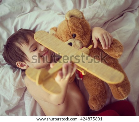 Happy kid playing with wooden toy airplane and Teddy bear in bedroom