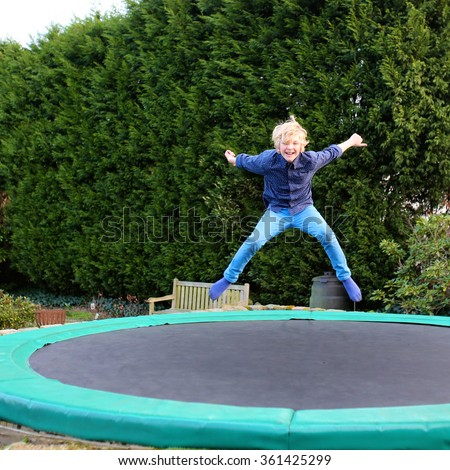 Happy kid plays outdoors in garden jumping high in the sky on trampoline. Active teenager boy having fun outdoors at early spring day. Healthy lifestyle concept. - stock photo
