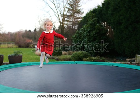 Happy kid plays outdoors in garden jumping high in the sky on trampoline. Active toddler having fun outdoors at early spring day. Healthy lifestyle concept. - stock photo