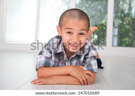 Happy kid posing on floor at home - stock photo