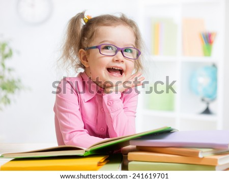 Happy kid reading books and dreaming - stock photo