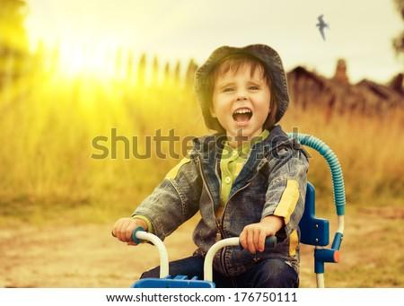 Happy kid riding a bike outdoors. - stock photo