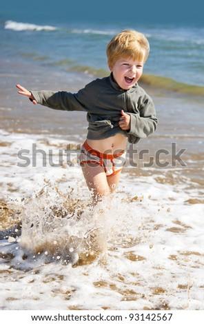 happy kid running on the sea beach - stock photo
