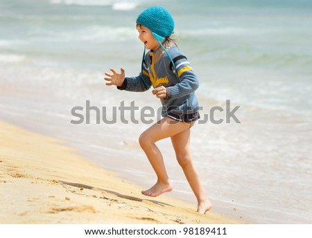 happy kid running on the sea beach