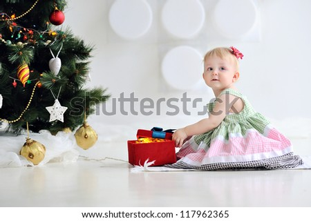 Happy kid sitting next to a Christmas tree with decorations. Christmas. Girl holding a box with a gift. A child in a beautiful dress. - stock photo