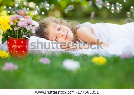 Happy kid sleeping on green grass outdoors in spring garden - stock photo