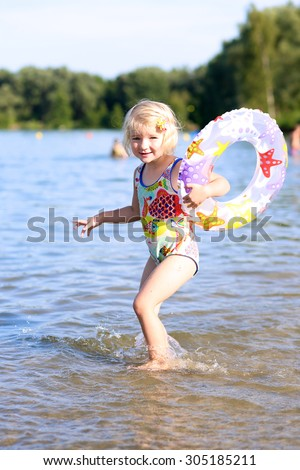 Happy kid swimming in the lake. Healthy smiling toddler girl relaxing in the water using inflatable ring. Active children summer vacation concept. - stock photo