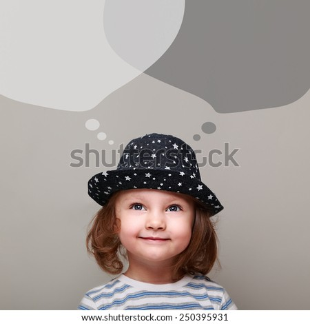 Happy kid thinking and looking up on chat bubbles above on grey background - stock photo