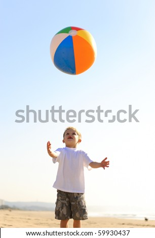 Happy kid throws his beach ball in the air and tries to catch it - stock photo