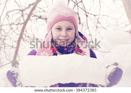 Happy kid winter day playing in the snow. Photos in retro style. - stock photo