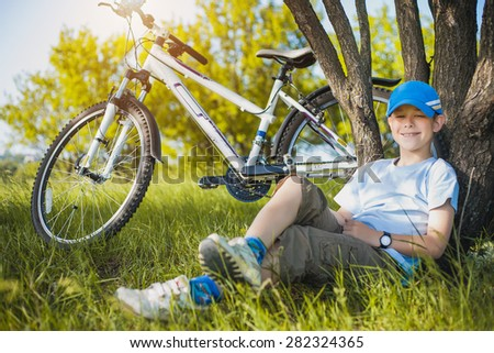 happy kid with a bicycle resting under a tree - stock photo