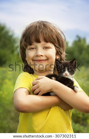 Happy kid with a kitten in her arms in nature