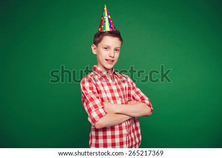 Happy kid with birthday cap looking at camera - stock photo