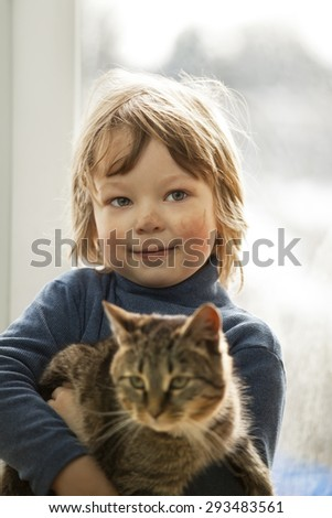 Happy kid with dirty face with cat in her arms in home - stock photo