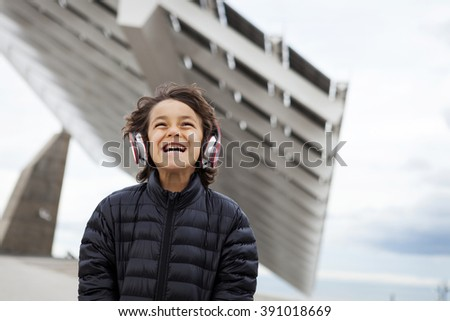 happy kid with headphone on a urban landscape