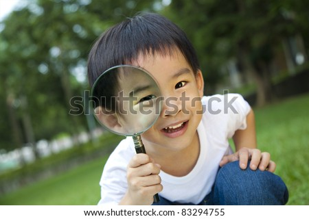 happy kid with magnifying glass - stock photo