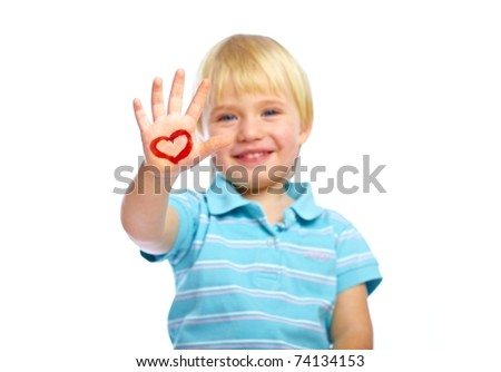Happy kid with painted heart shape on his hand - stock photo