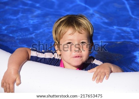 Happy kid with sun protection swimwear smiling in the swimming pool - stock photo