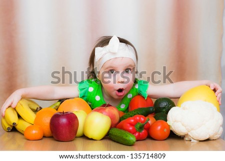 Happy Kid with vegetables and fruits sitting at the table.