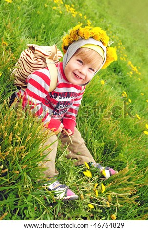 happy kid with wreath of dandelion flowers on the blooming meadow - stock photo