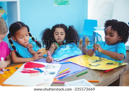 Happy kids all drawing pictures at their desk