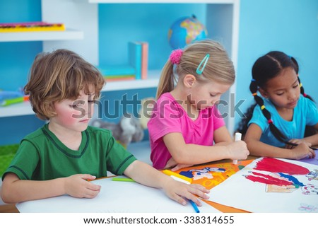 Happy kids all drawing pictures at their desk - stock photo