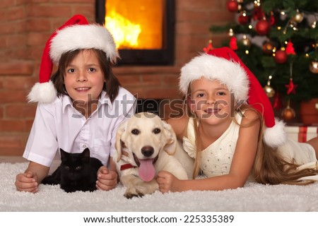 Happy kids and their pets celebrating Christmas together - cat and dog laying with owners - stock photo