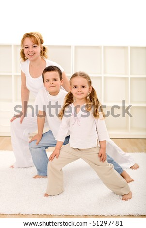 Happy kids and woman doing some gymnastic exercises indoors