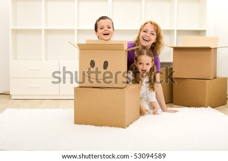 Happy kids and woman having fun in their new home playing among cardboard boxes