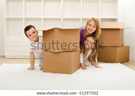 Happy kids and woman in a new home unpacking and having fun