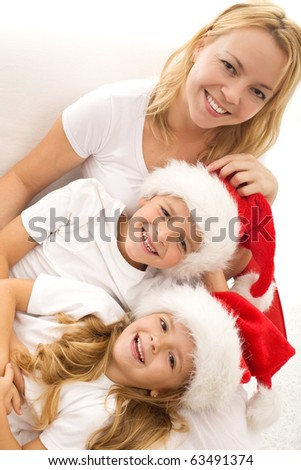 Happy kids and woman relaxing on the white sofa at christmas time - closeup - stock photo