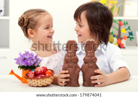 Happy kids at easter time laughing - with large chocolate bunnies and colorful eggs - stock photo