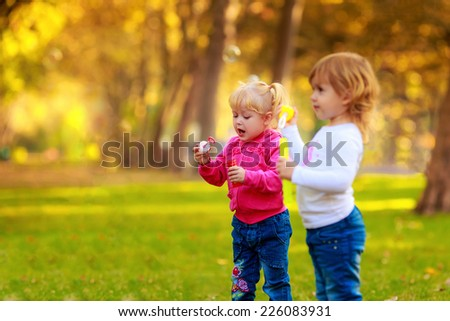 Happy kids blow bubbles outdoors - stock photo