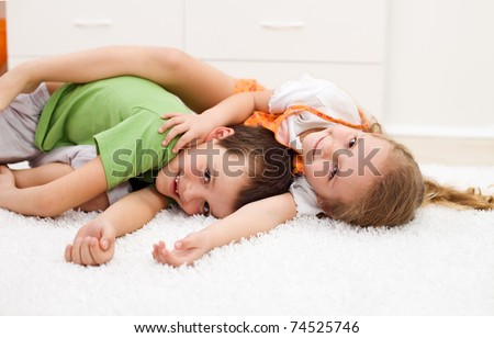 Happy kids boy and girl wrestling in their room laying on the floor - focus on the girl - stock photo