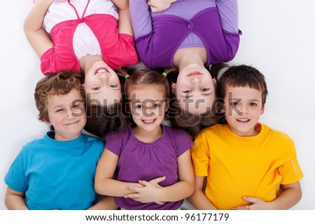 Happy kids - boys and girls - laying on the floor smiling - stock photo