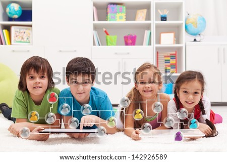 Happy kids connecting to social networks and friends - using tablet computers - stock photo