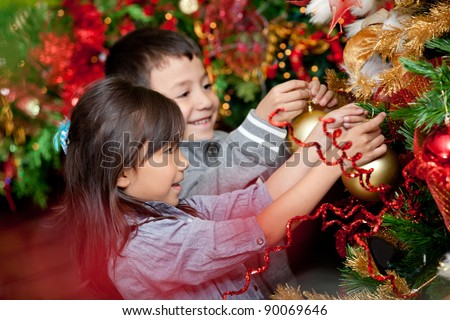 Happy kids decorating a Christmas tree with balls - stock photo