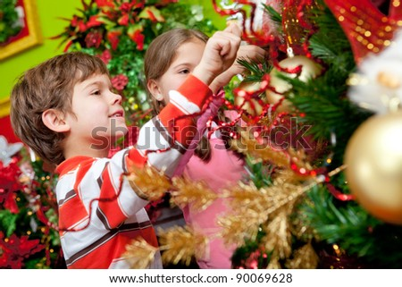 Happy kids decorating a Christmas tree with ornaments - stock photo