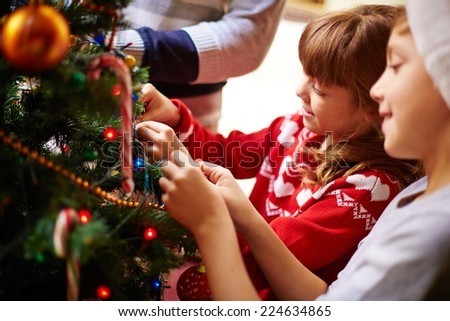 Happy kids decorating Christmas tree for holiday - stock photo