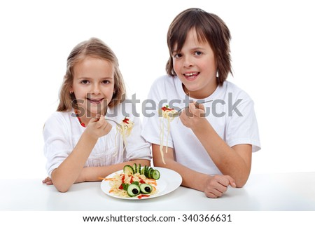 Happy kids eating a pasta dish - isolated - stock photo