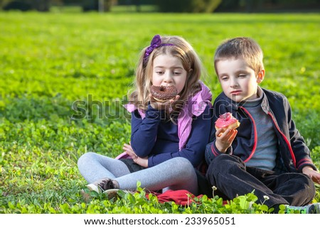 happy kids eating donuts sitting on the green grass in the park