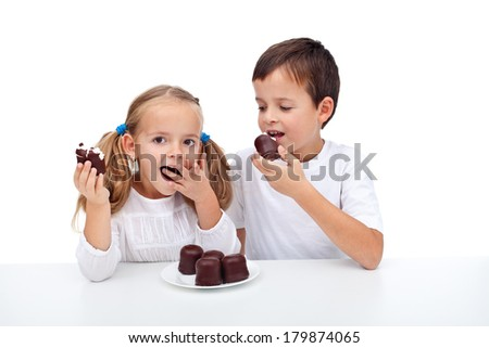 Happy kids eating whipped cream and chocolate dessert - isolated - stock photo