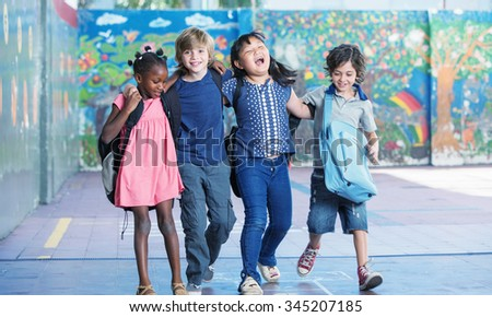 Happy kids embracing and smiling in the elementary schoolyard. Interracial  friendship. - stock photo