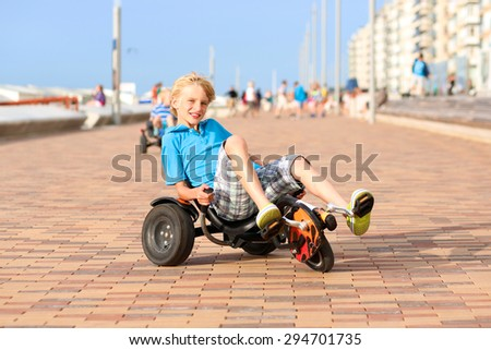 Happy kids enjoying active holidays on the beach. Sportive boy riding pedal car along the promenade on a summer day at sunset.  - stock photo