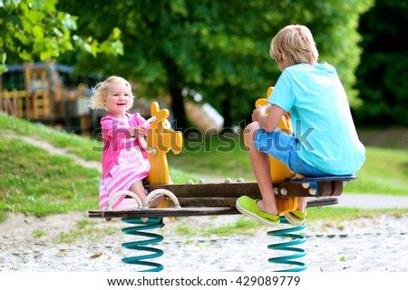 Happy kids enjoying active summer vacation. Adorable toddler girl, having fun outdoors swinging with her brother on playground in the park on a sunny day. - stock photo