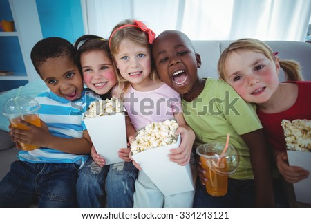 Happy kids enjoying popcorn and drinks while sitting on the couch - stock photo