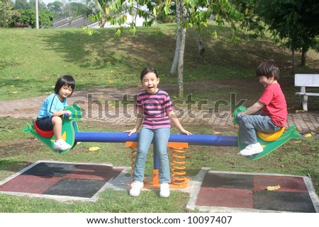 Happy kids enjoying seesaw at the playground in the park - stock photo