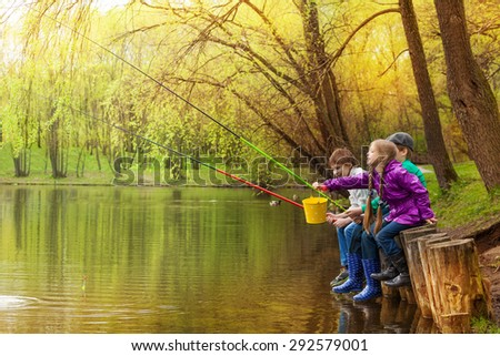 Happy kids fishing together near beautiful pond - stock photo